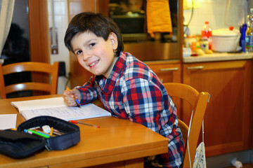 smiling boy does homework at his home
