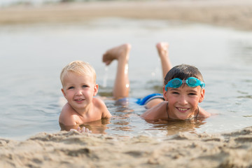 Portrait of two happy kids lying in water at summer beach.