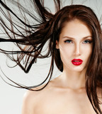 Beautiful woman with magnificent hair. Flying hair. Red lipstick