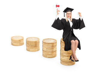 Female graduate sitting on a pile of coins