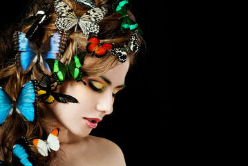 Young  beautiful woman with butterflies in her hair
