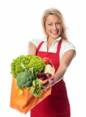 Frau mit Schürze hält Tasche mit Gemüse