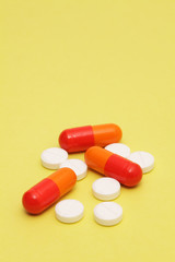 Colorful pills on yellow background
