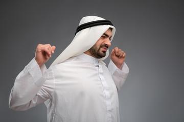 Arab man raising his hands being tired