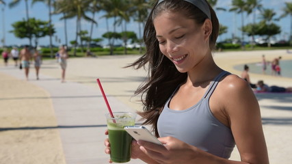 Smartphone fitness woman drinking green smoothie