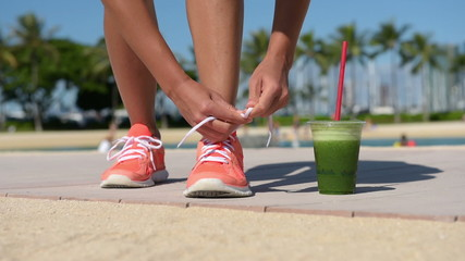 Running woman runner with green vegetable smoothie