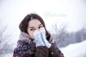 Winter time: Young girl in mittens outdoors in winter scene