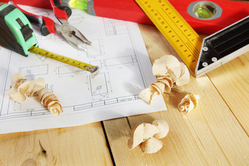 Various working tools lie on the wooden workbench