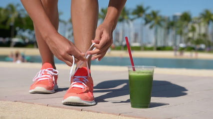 Running woman with green vegetable smoothie