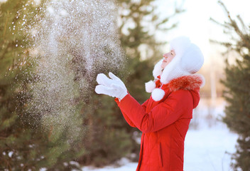 Happy woman having fun throws up snow in winter day