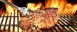 Leinwandbild Motiv Grilled Pork Chop on Flaming BBQ Grill.