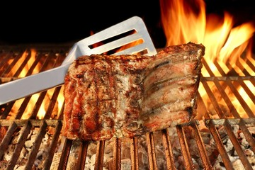 Grilled Pork Chop on Flaming BBQ Grill.