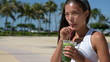 Healthy woman drinking green vegetable smoothie