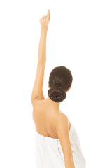 Back view woman wrapped in towel pointing up