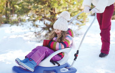 Mother sledding child in winter day