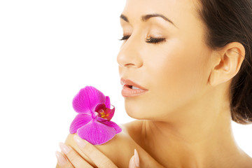 Naked woman with purple orchid petal on shoulder