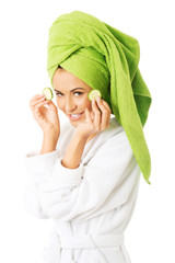 Woman in bathrobe applying cucumber on eyes