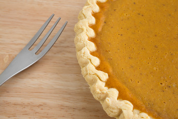 Pumpkin pie and fork on table