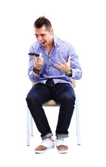 Young caucasian handsome man sitting on the chair isolated