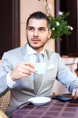 Young businessman drinking a cup of coffee