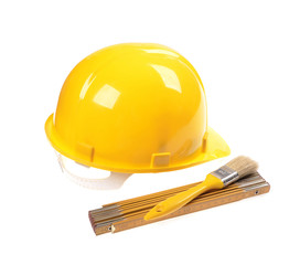 Yellow helmet ,  meter building and brush isolated on white
