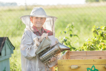 Teenage beekeeper wearing protective clothing