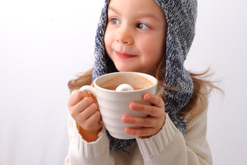 A cute little girl drinking hot chocolate with marshmallow