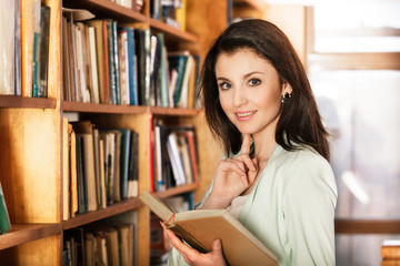Woman reading a book in front of bookshelves