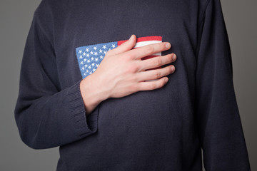 man holding hand on his heart with american flag, patriotism