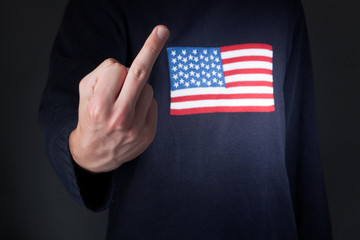 man with american flag on shirt showing middle finger