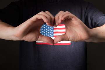 man with american flag on shirt showing heart of his hands