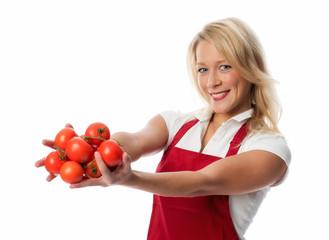 Hausfrau mit roter Schürze hält Tomaten