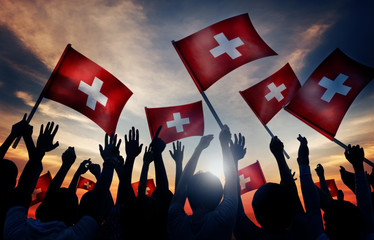 Silhouettes of People Holding Flag of Switzerland Concept