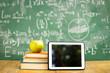 Leinwanddruck Bild - Digital tablet and apple on stack of books