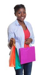 Lachende Frau aus Afrika zeigt ihre Einkaufstaschen