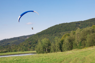 Blue paraglider flying in beatiful nature