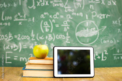 Digital tablet and apple on stack of books - 76829872