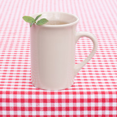 cup with mint tea on checkerboard table