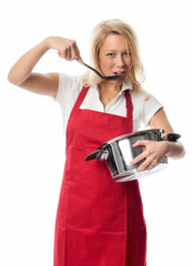 Frau hält einen Topf und probiert mit einem Löffel