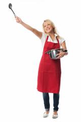 Frau mit roter Schürze hält einen Kochlöffel hoch