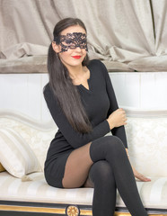 Young woman in a mask on the couch