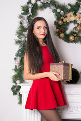 Girl in a short red dress with a gift in hand on background fire