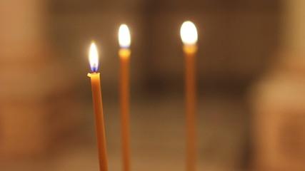 Three orange burning candle in church