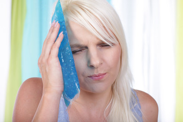 Frau mit Eisbeutel am Gesicht