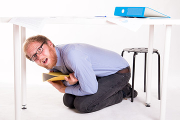 Scared man huddled under a desk in the office