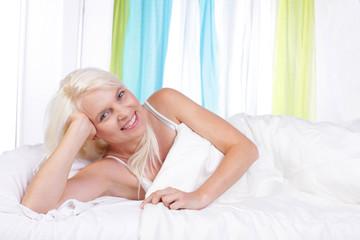 Junge Frau entspannt morgens im Bett