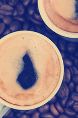 Fresh creamy espresso over roasted coffee beans background