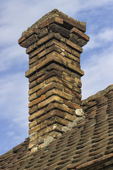 Old brick chimney with old tiles roof