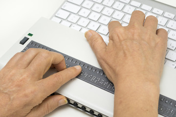 Blind person reads on braille display from computer screen