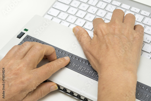 Blind person reads on braille display from computer screen - 76834824